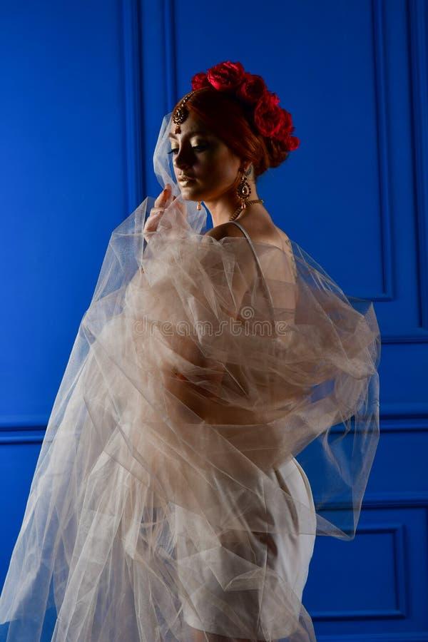 Foto da forma da menina bonita sob o véu branco e de flores vermelhas em sua cabeça no fundo azul foto de stock