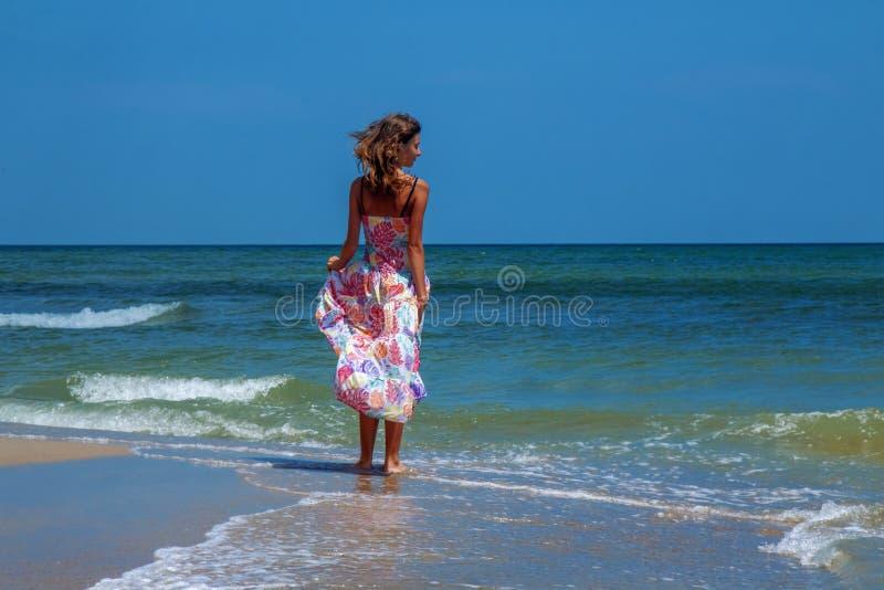 Foto da forma da menina moreno nova bonita feliz no mar contra a água e o céu azul _curso, felicidade, verão resto, liberdade foto de stock