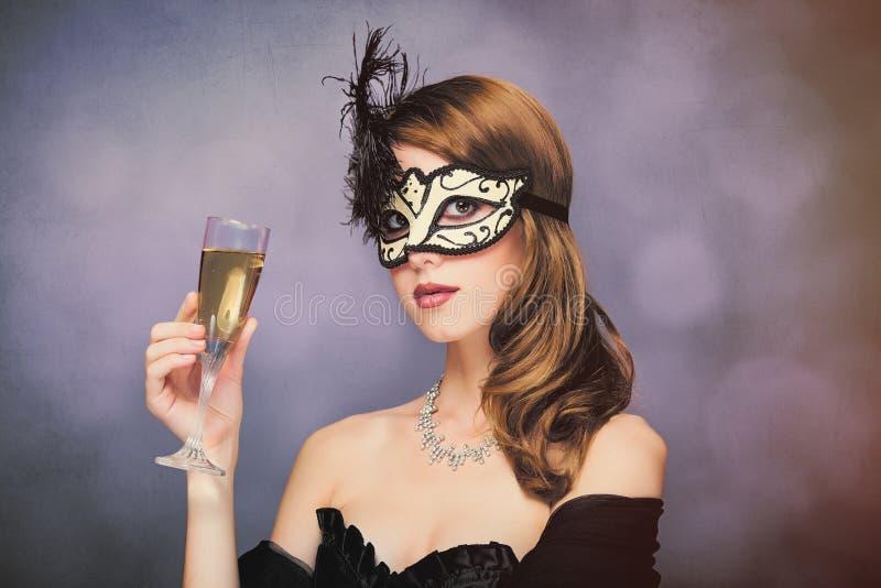 Foto da jovem mulher bonita na máscara com o copo de vinho do champag fotografia de stock