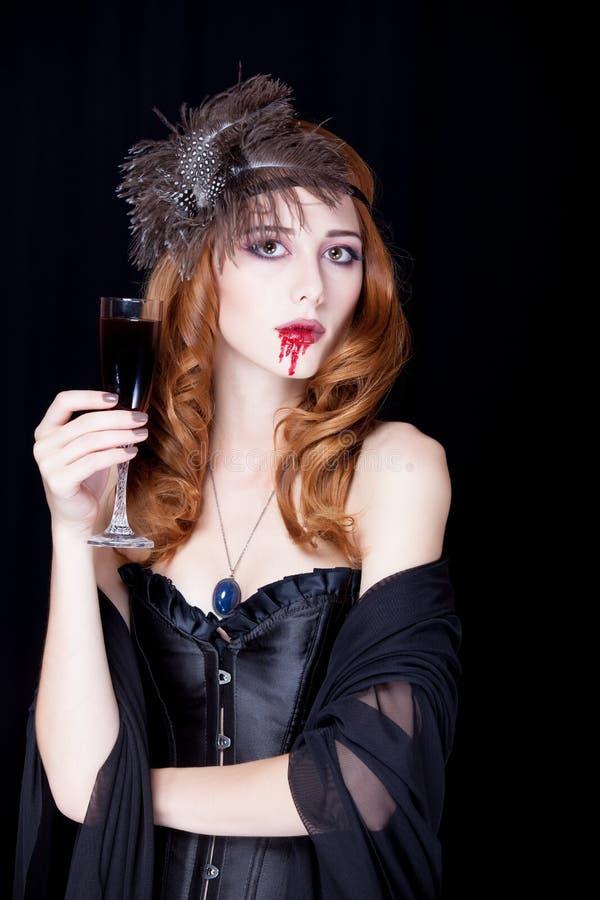 Foto da jovem mulher bonita no caráter do vampiro com vidro o fotos de stock royalty free