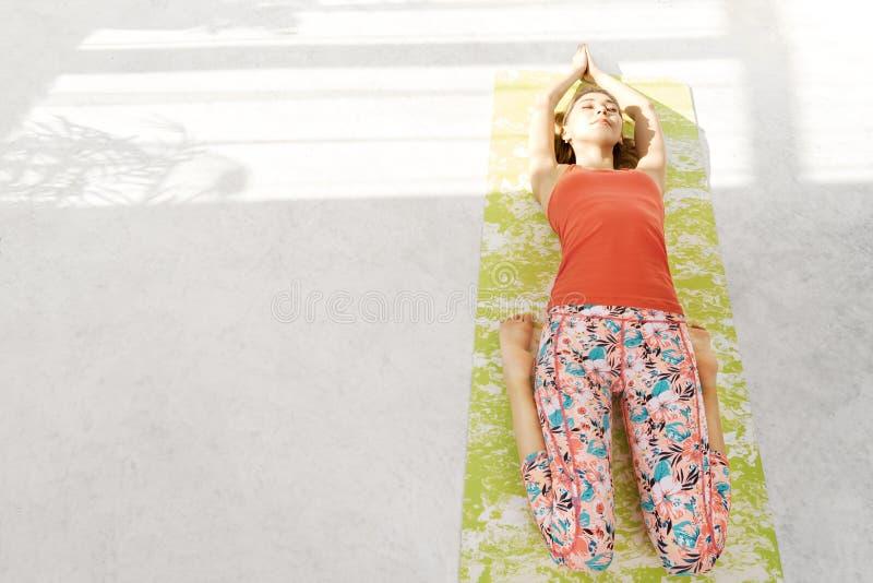Foto da jovem mulher bonita que encontra-se em uma esteira da ioga, descansando ap?s ter feito os exerc?cios da ioga, encontrando imagem de stock