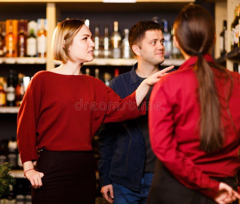 Foto da jovem mulher, do homem e do vendedor da parte traseira na loja com vinho foto de stock