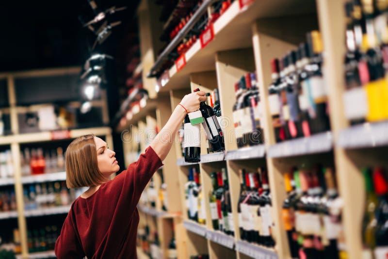 Foto da jovem mulher na loja de vinho imagem de stock royalty free