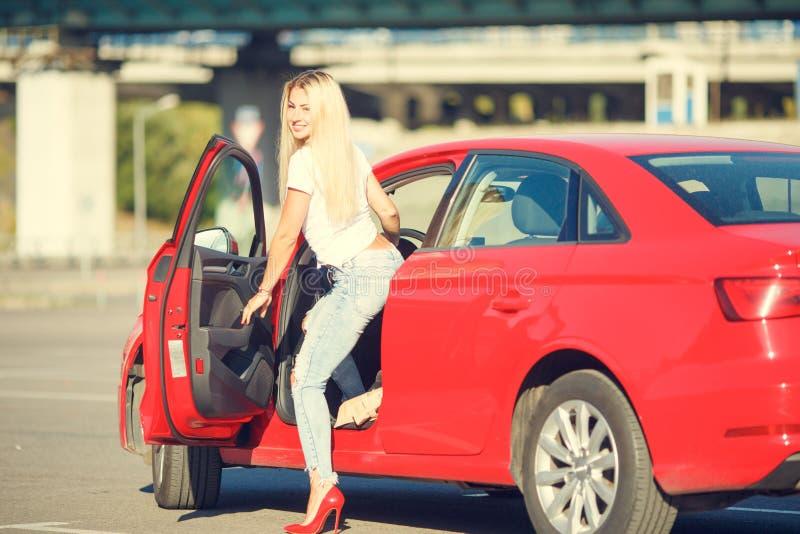 Foto da jovem mulher que sae do carro vermelho foto de stock
