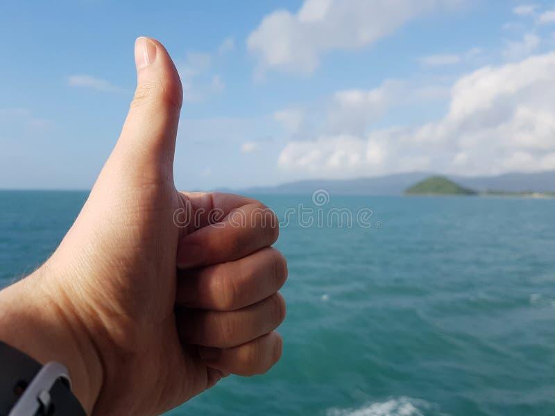 Foto da mão com o dedo ascendente e a costa de mar, céu nebuloso foto de stock royalty free