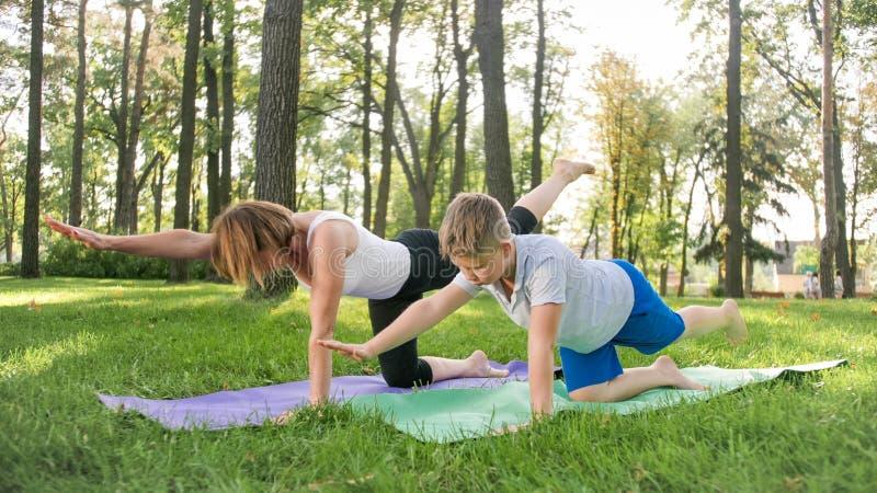 Foto da m?e com seu asana praticando da ioga do filho do adolescente na grama no parque Fam?lia que faz o outtodr da aptid?o e do fotografia de stock