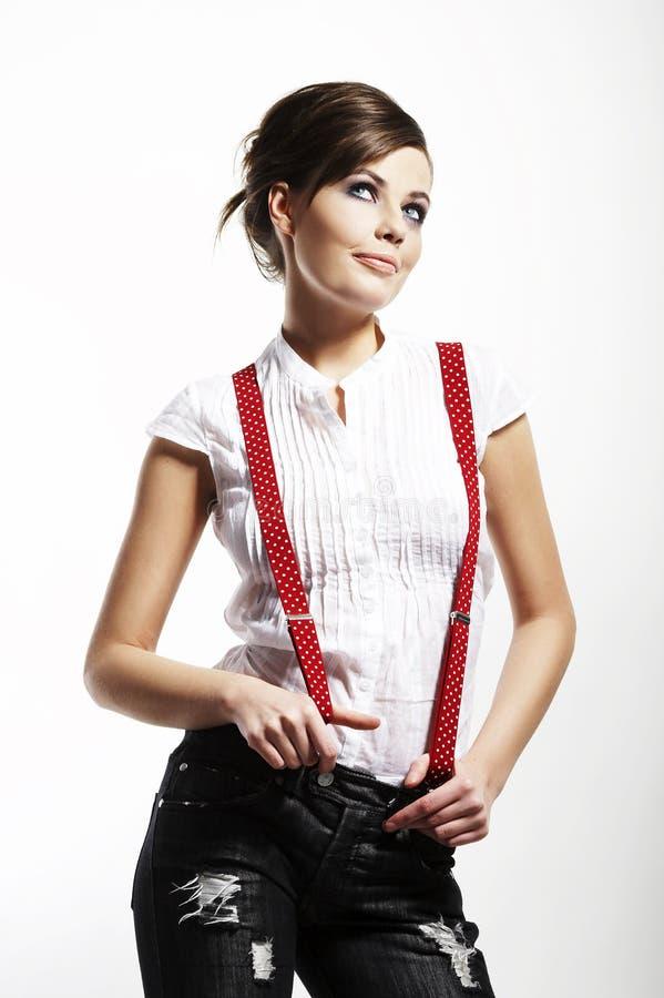 Foto da menina bonita que estica suspenders fotos de stock