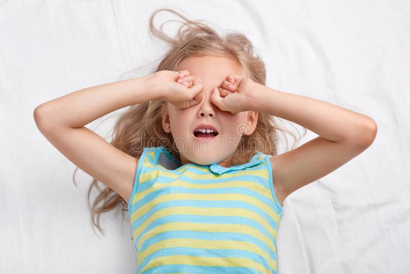 A foto da menina de cabelo clara de vista agradável fricciona os olhos, quer dormir, vestido no nightwear, mentiras na cama confo fotos de stock royalty free
