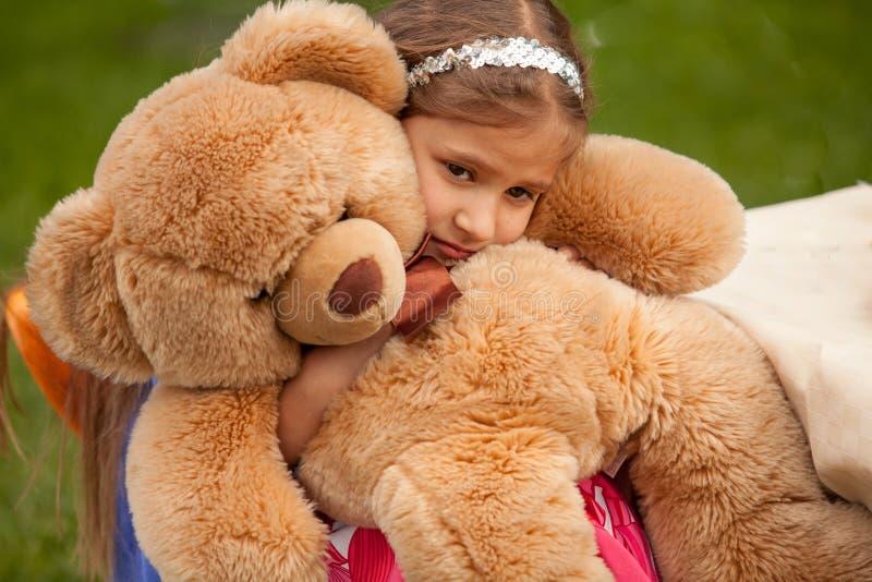 Foto da menina triste que abraça o urso de peluche foto de stock