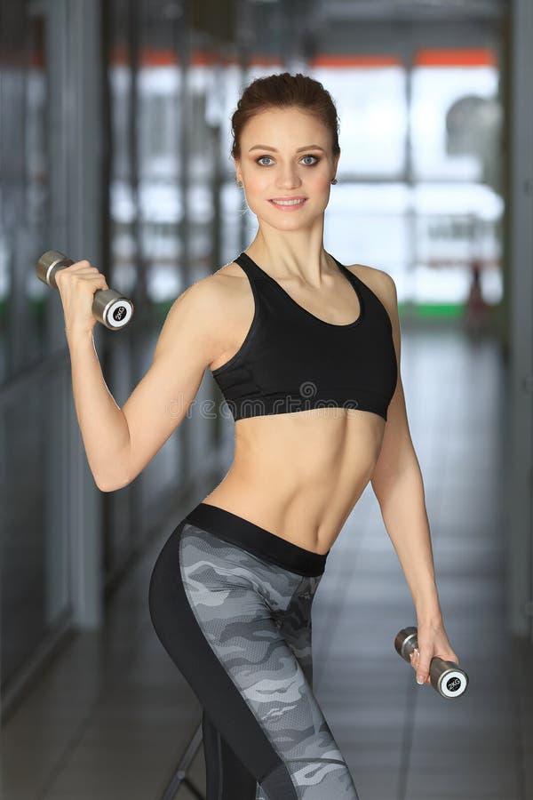 Foto da moça atlética que está com pesos fotos de stock