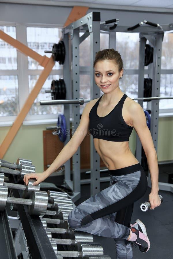 Foto da moça atlética que faz um exercício da aptidão com pesos no gym fotos de stock royalty free