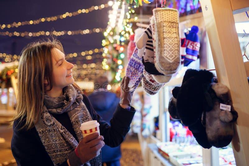 Foto da moça com vidro do café nas mãos perto da loja com os mitenes na caminhada do inverno na cidade imagens de stock royalty free
