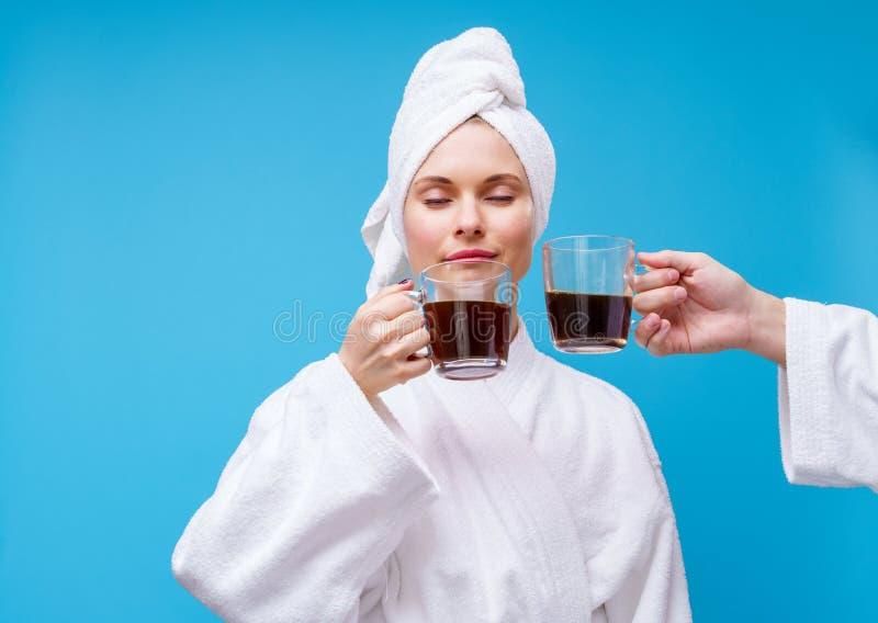 Foto da moça no revestimento e na toalha brancos em sua cabeça com a caneca de café fotos de stock royalty free