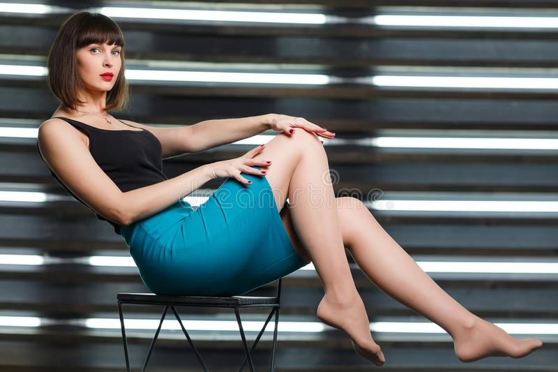 Foto da morena nova que senta-se na cadeira perto da janela com cortinas imagens de stock