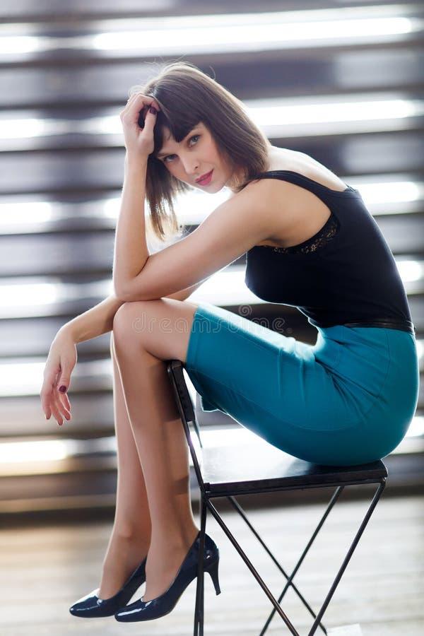 Foto da morena nova que senta-se na cadeira perto da janela com cortinas imagens de stock royalty free