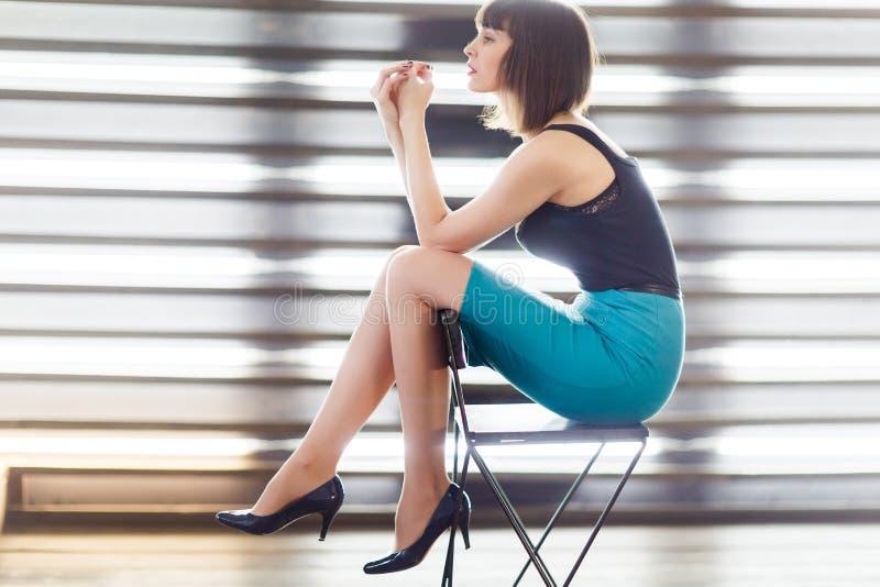 Foto da morena nova que senta-se na cadeira perto da janela com cortinas fotos de stock