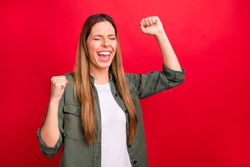 Foto da mulher aspirada agradável bem sucedida extático que comemora sua vitória quando isolado com fundo vermelho imagem de stock royalty free