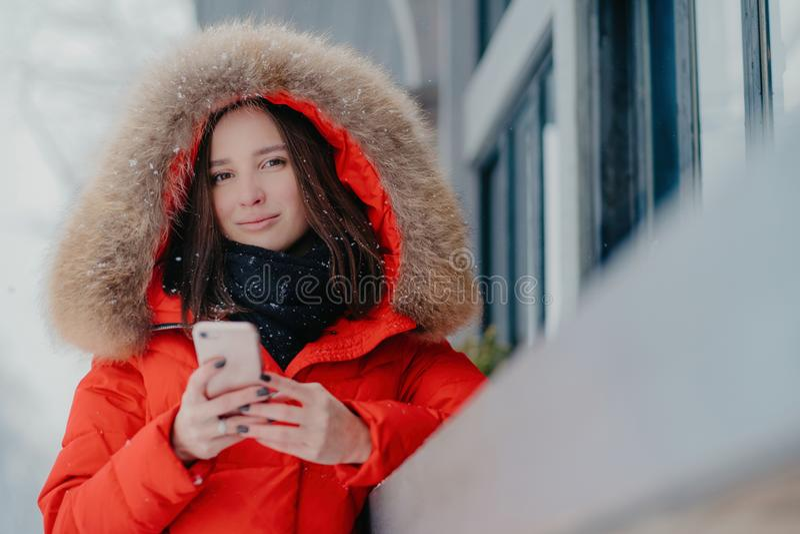 A foto da mulher atrativa guarda o dispositivo moderno moderno, veste o revestimento vermelho com hoody, verificações envia e-mai fotos de stock