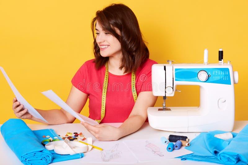A foto da mulher atrativa nova que trabalha na oficina, veste a camisa vermelha, sentando-se na tabela branca com costurar os equ fotos de stock