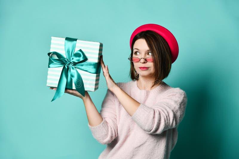 Foto da mulher bonita no chapéu de feltro que guarda a caixa de presente atual fotografia de stock royalty free