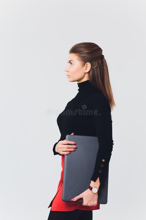 A foto da mulher bonita 20s que sorri e que usa o computador com pés cruzou-se isolado sobre o fundo branco fotografia de stock