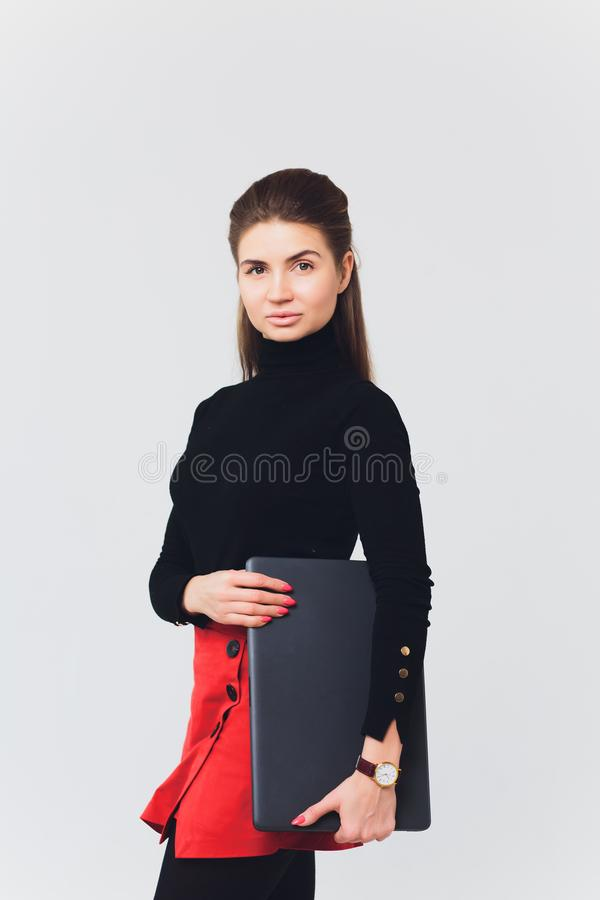 A foto da mulher bonita 20s que sorri e que usa o computador com pés cruzou-se isolado sobre o fundo branco imagem de stock royalty free