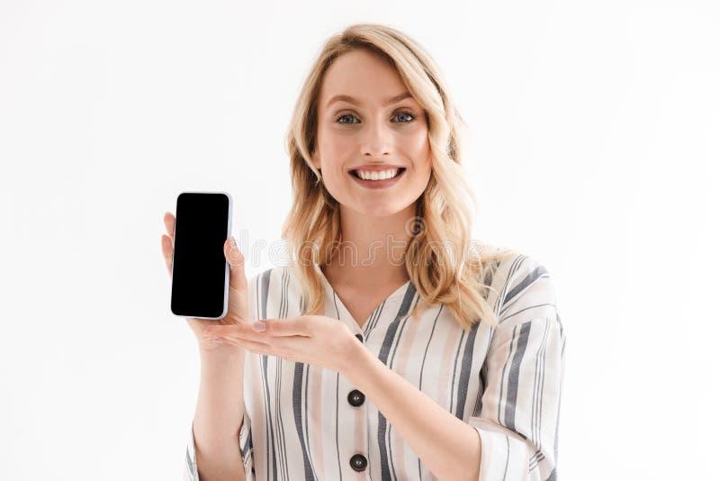 Foto da mulher caucasiano que sorri na c?mera e que guarda o smartphone foto de stock