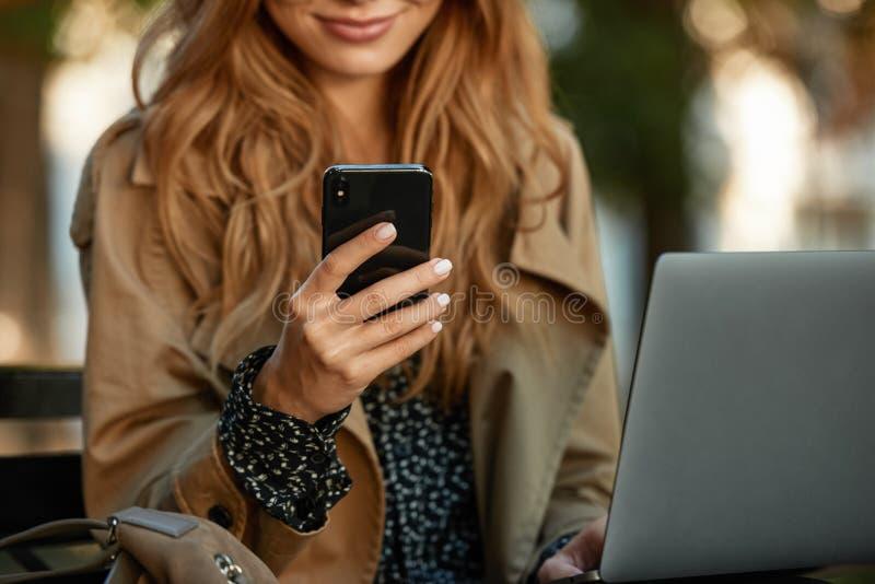 Foto da mulher de negócios que usa o telefone celular e o portátil ao sentar-se no banco na aleia ensolarado fotos de stock royalty free