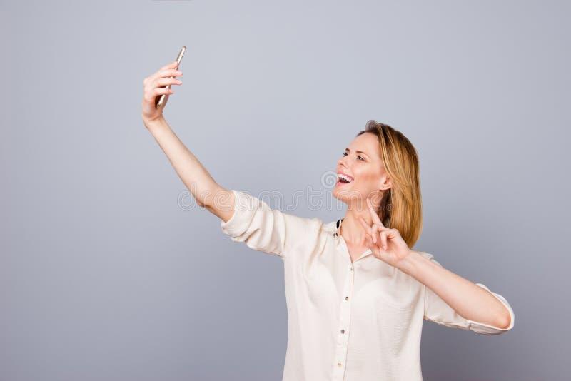 Foto da mulher de riso feliz consideravelmente nova que toma o selfie usando h fotos de stock royalty free
