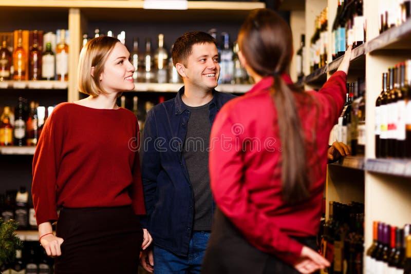 Foto da mulher, do homem e do vendedor da parte traseira na loja com vinho imagens de stock