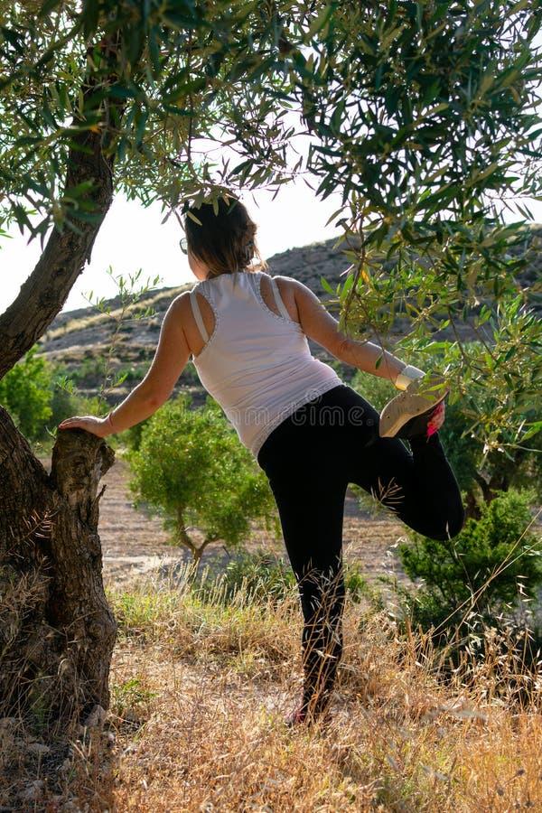 Foto da mulher envelhecida média na roupa dos esportes que pratica o esticão exterior imagens de stock
