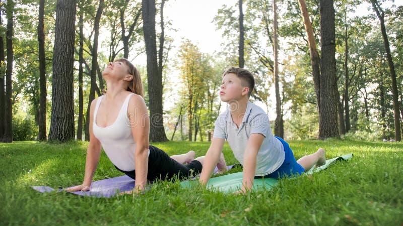 Foto da mulher envelhecida m?dia com 12 anos de ioga praticando do adolescente idoso e meditar no parque fam?lia que relaxa e fotografia de stock royalty free