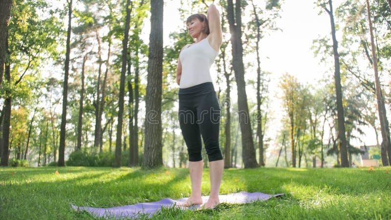 Foto da mulher envelhecida meio na roupa dos sportrs que pratica a ioga fora no parque Mulher envelhecida m?dia que estica e foto de stock