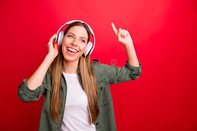 Foto da mulher fanático bonito agradável de apreciação ocasional que escuta seu músico favorito quando isolado com fundo vermelho fotos de stock royalty free