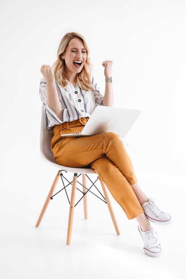 Foto da mulher feliz europeia que veste a roupa ocasional usando o port?til ao sentar-se na cadeira imagem de stock