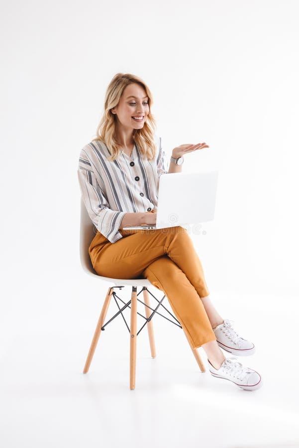 Foto da mulher loura europeia que veste a roupa ocasional usando o port?til e realizando o copyspace ao sentar-se na cadeira fotografia de stock royalty free