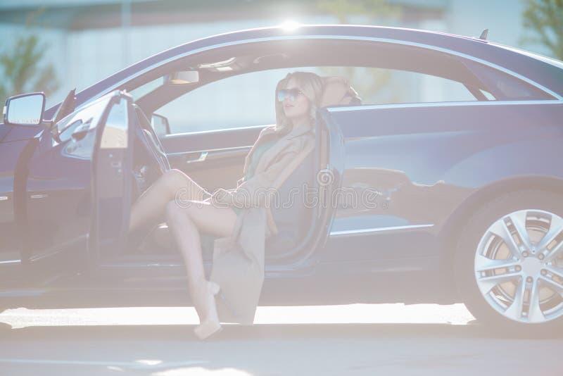Foto da mulher loura feliz com os vidros e o vestido longo que sentam-se no carro com estar aberto foto de stock royalty free