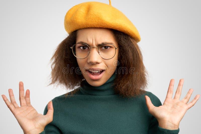 A foto da mulher negra surpreendida, exclama com expressão surpreendida Menina de cabelo escura irritada descontentada com algo imagens de stock royalty free