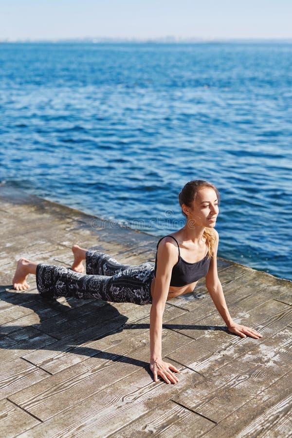 Foto da mulher nova dos esportes para fazer exercícios da ioga na praia com fundo do mar Sentimento tão confortável e para relaxa fotos de stock royalty free