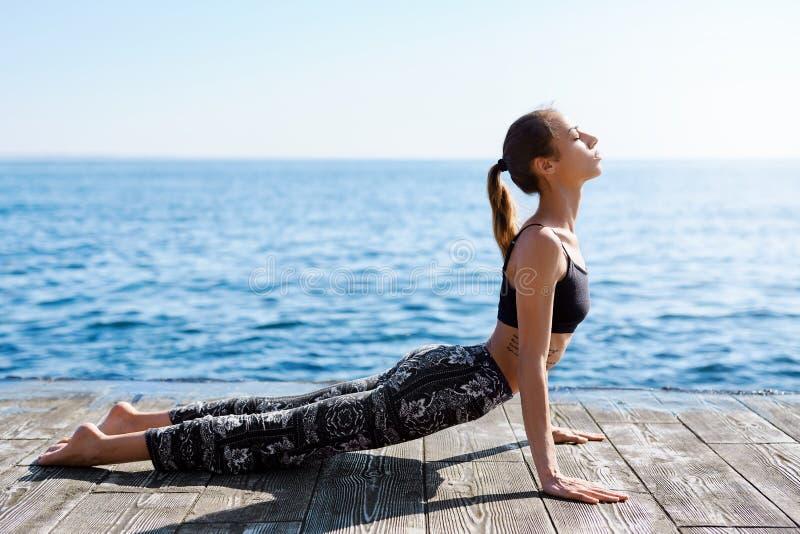 Foto da mulher nova dos esportes para fazer exercícios da ioga na praia com fundo do mar Sentimento tão confortável e para relaxa imagens de stock royalty free