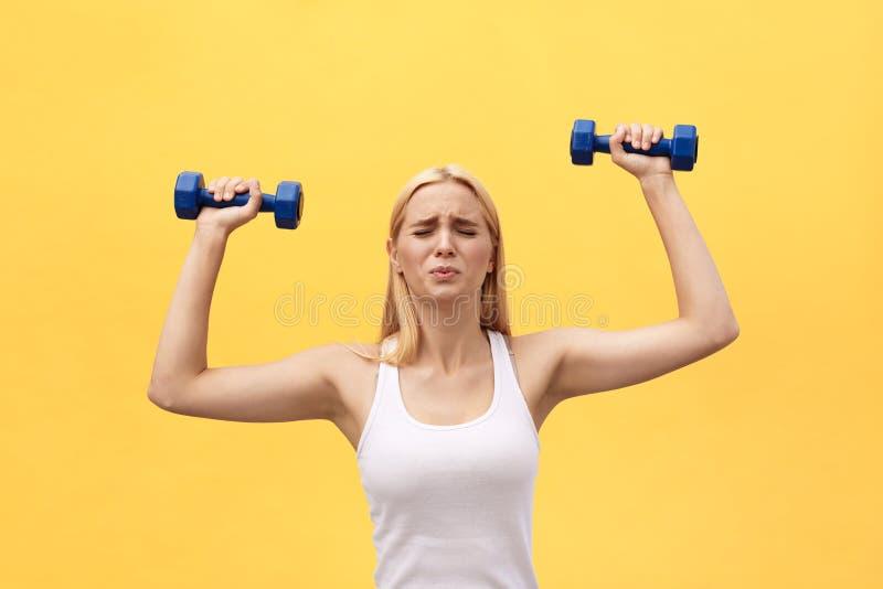 Foto da mulher nova séria dos esportes para fazer exercícios com os pesos isolados sobre o fundo amarelo da parede imagens de stock