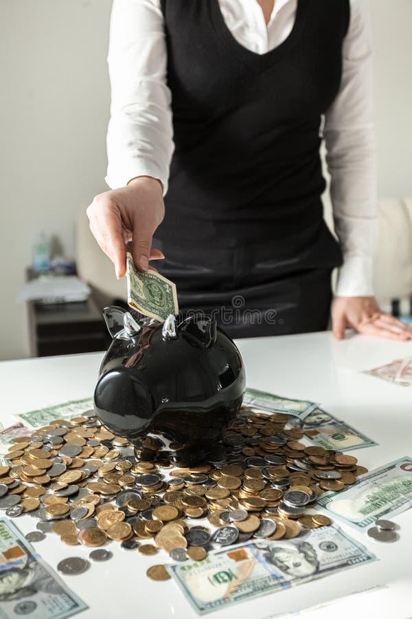 Foto da mulher que introduz o dólar no moneybox do porco foto de stock royalty free