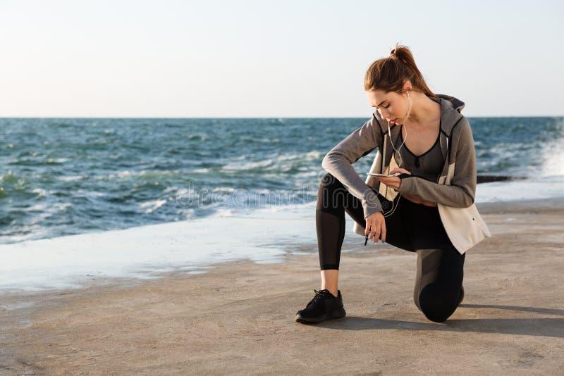 Foto da mulher saudável nova do esporte que senta-se no joelho, verificando mes fotos de stock