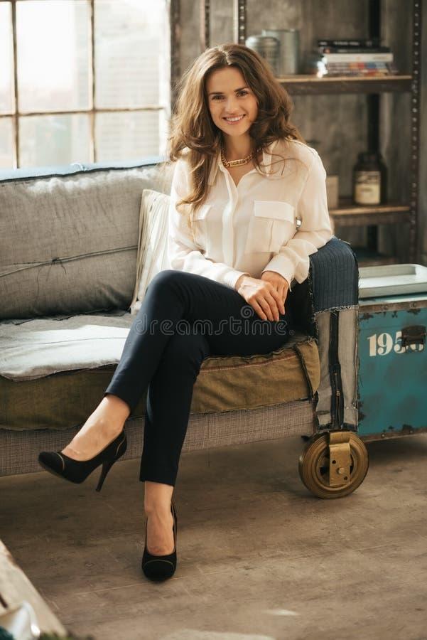 Foto da mulher triguenha à moda que senta-se no treinador na sala do sótão fotografia de stock