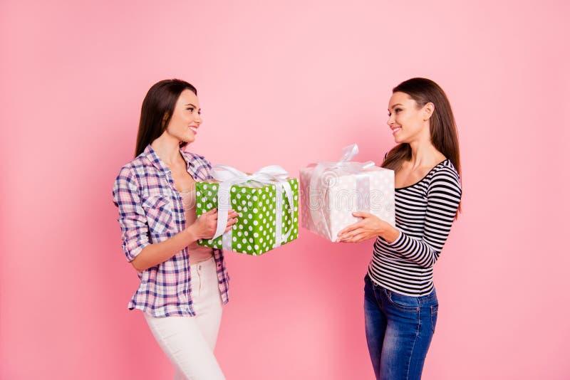 Foto da opinião lateral do perfil da bolsa de estudo encantador dos companheiros das senhoras que envia recebendo grandes giftbox fotos de stock