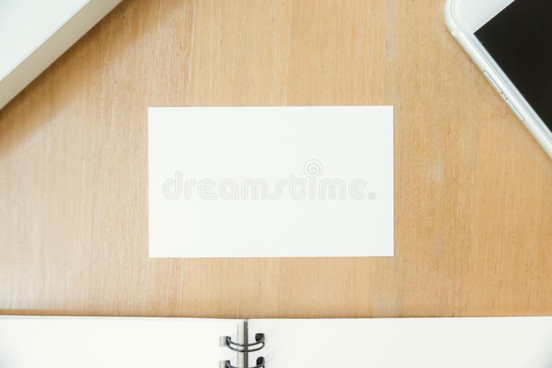 Foto da opinião superior do close up que mostra o cartão branco vazio e que usa o portátil e o telefone celular modernos na tabel imagem de stock