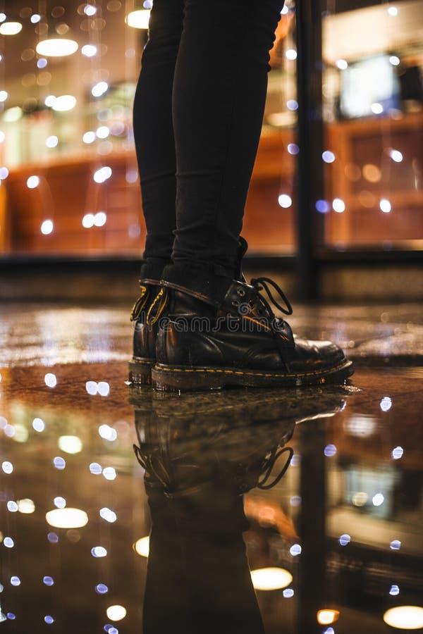 Foto da pessoa que veste calças de brim cabidas pretas e o Dr. preto botas das martas que estão em telhas de assoalho pretas foto de stock royalty free