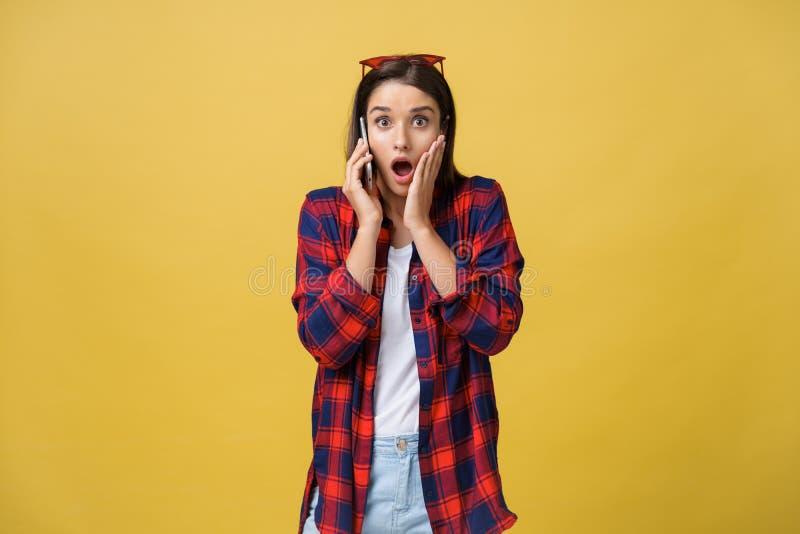 Foto da posição bonita nova chocada emocional da mulher isolada sobre o fundo amarelo usando o telefone celular que olha de lado imagens de stock royalty free