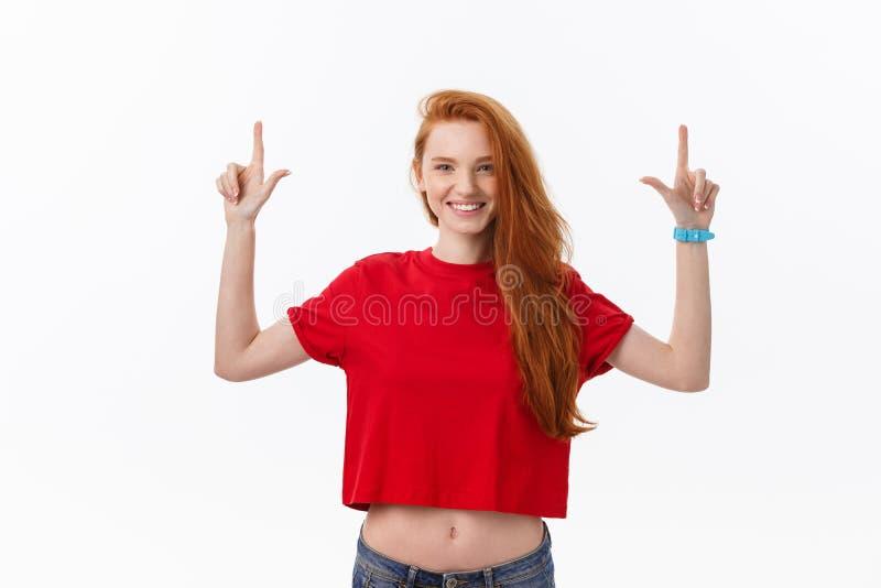 Foto da posição feliz da jovem mulher isolada sobre o fundo branco da parede Olhando a câmera que mostra apontar do copyspace fotografia de stock