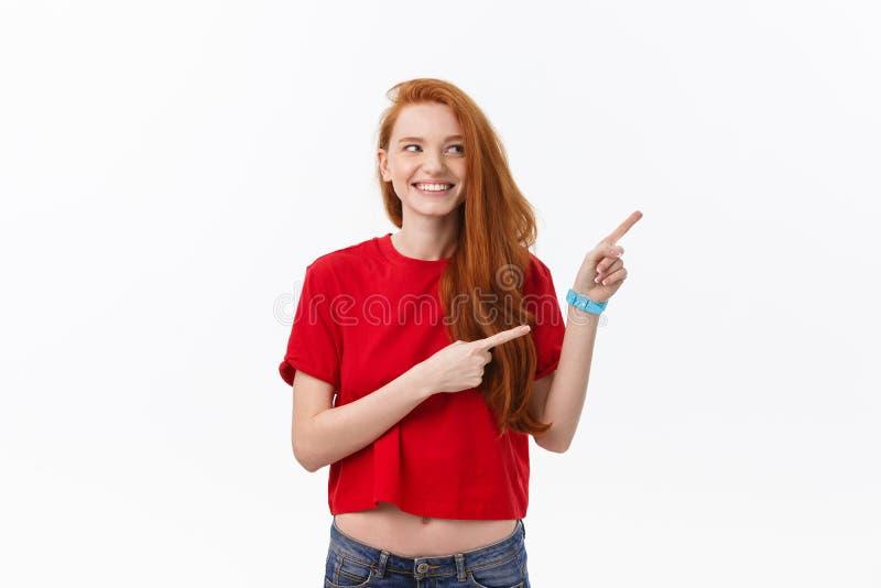 Foto da posição feliz da jovem mulher isolada sobre o fundo branco da parede Olhando a câmera que mostra apontar do copyspace imagem de stock royalty free